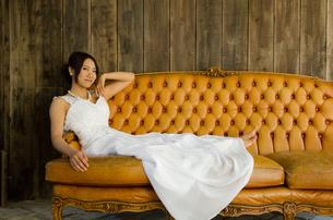 大きなソファに座るドレス姿の女性の素材 [FYI01078309]