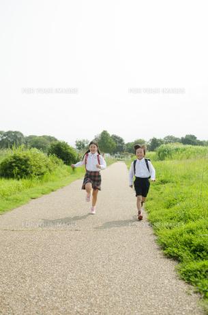 ランドセルを背負って走る小学生2人の素材 [FYI01078318]