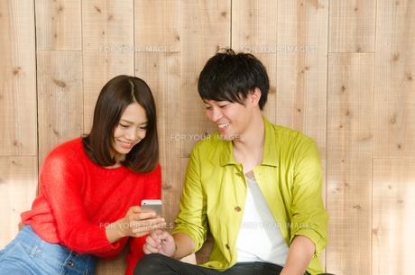スマホを見ながら笑うカップルの素材 [FYI01078323]