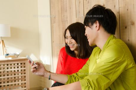 スマホを見ながら笑うカップルの素材 [FYI01078328]