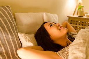 ベッドで横になる女性の素材 [FYI01078333]