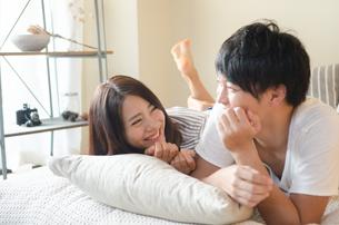 ベッドの上で笑うカップルの素材 [FYI01078335]