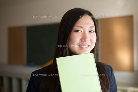 ノートを持って笑っている女子高校生の素材 [FYI01078339]