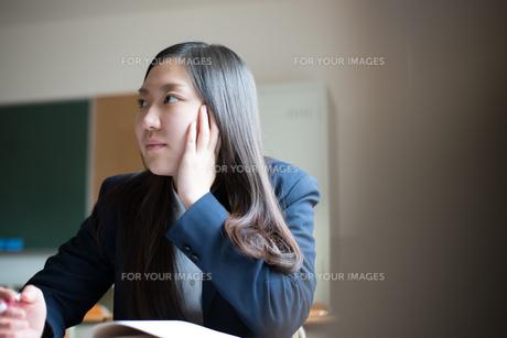 机に座って話を聞いている女子高校生の素材 [FYI01078340]