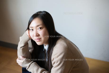 座ってこちらを見ている女子高校生の素材 [FYI01078346]