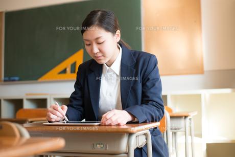 タブレットで勉強をしている女子高校生の素材 [FYI01078355]