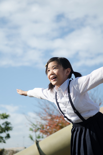 飛ぶポーズをしている小学生の女の子の素材 [FYI01078358]