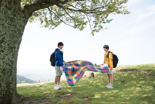 山頂でピクニックマットを広げている男女の素材 [FYI01078362]