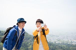 山頂で写真を撮っている男女の素材 [FYI01078374]