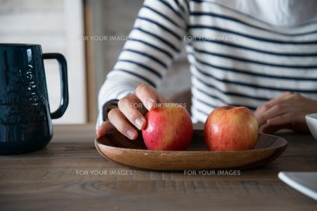 ふたつのりんごを触っている女性の手元の素材 [FYI01078378]