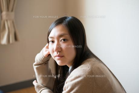 座ってこちらを見ている女子高校生の素材 [FYI01078382]