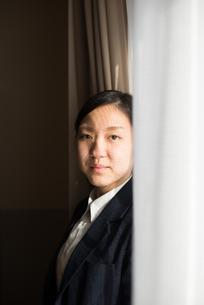 カーテンの横でこちらを見ている女子高校生の素材 [FYI01078383]