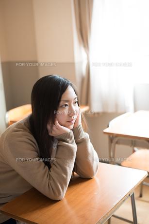 机で頬杖をついている女子高校生の素材 [FYI01078388]