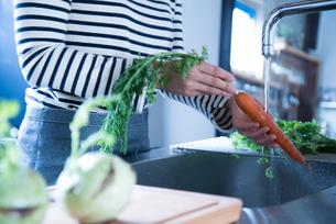 キッチンで野菜を洗っている女性の手元の素材 [FYI01078391]
