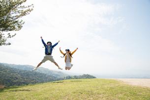 山頂でジャンプをしている男女の素材 [FYI01078392]