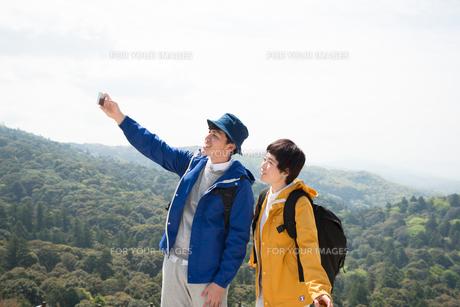 山頂で写真を撮っている男女の素材 [FYI01078393]