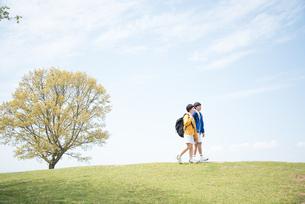 芝生の上を歩いている男女の素材 [FYI01078395]
