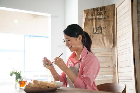 エプロンをしてパスタを食べようとしている女性の素材 [FYI01078398]