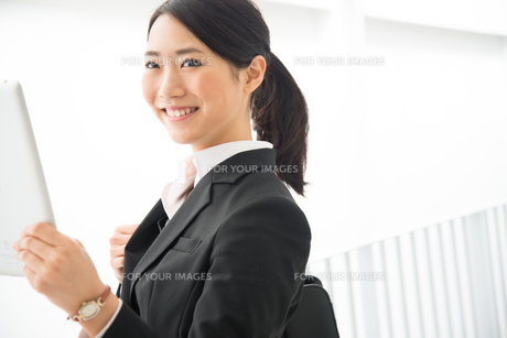 タブレットを持っているスーツ姿の女性の素材 [FYI01078402]