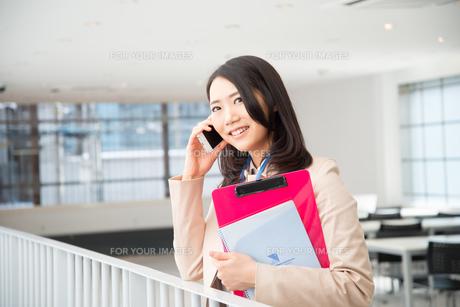 ファイルを持って電話をしている女性の素材 [FYI01078403]