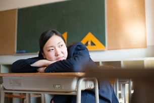 机の上で手を組んでいる女子高校生の素材 [FYI01078408]