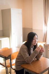教室でパンを食べている女子高校生の素材 [FYI01078410]