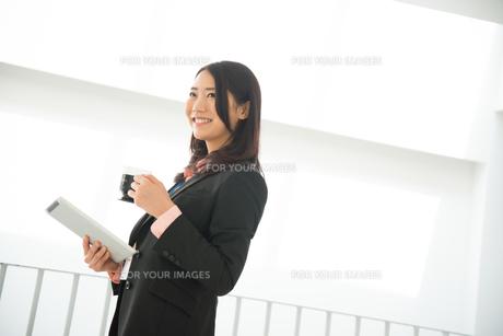 タブレットとコーヒーを持って笑っている女性の素材 [FYI01078413]