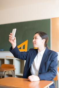 教室で自撮りをしている女子高校生の素材 [FYI01078418]