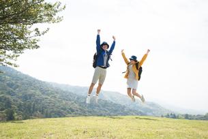 山頂でジャンプをしている男女の素材 [FYI01078425]