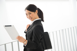 タブレットを見ているスーツ姿の女性の素材 [FYI01078427]