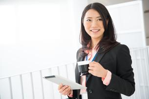 タブレットとコーヒーを持って笑っている女性の素材 [FYI01078428]