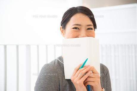 スケジュール帳を持って笑っている女性の素材 [FYI01078432]