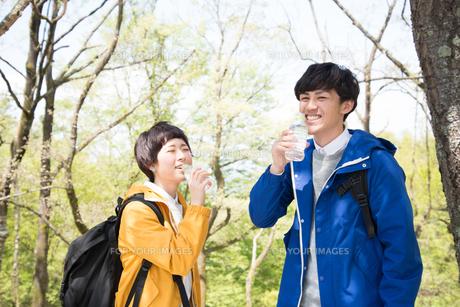 森の中で水を飲んでいる男女の素材 [FYI01078434]
