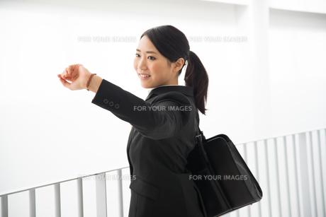 時計を見ているスーツ姿の女性の素材 [FYI01078437]