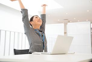 ノートパソコンの前で伸びをしている女性の素材 [FYI01078438]