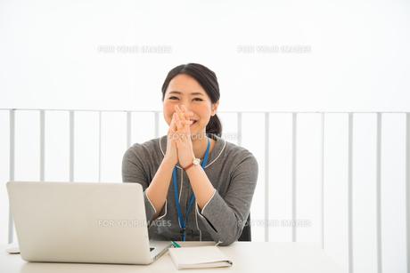ノートパソコンの前で笑っている女性の素材 [FYI01078443]