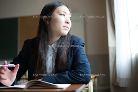机に座って窓の外を眺めている女子高校生の素材 [FYI01078449]