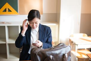 教室で携帯電話をいじっている女子高校生の素材 [FYI01078451]