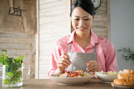 エプロンをしてパスタを食べようとしている女性の素材 [FYI01078452]