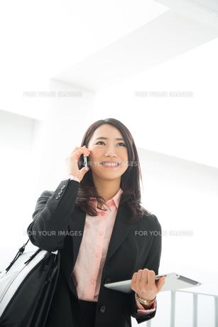 タブレットを持って電話をしている女性の素材 [FYI01078464]