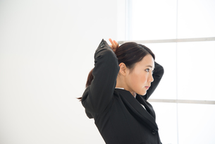 髪を結んでいるスーツ姿の女性の素材 [FYI01078469]