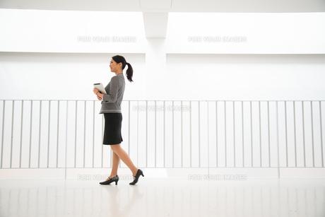 タブレットを抱えて歩いている女性の素材 [FYI01078476]