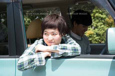 車から乗り出して笑う女性の素材 [FYI01078481]