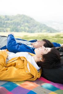 ピクニックマットの上に寝転がる男女の素材 [FYI01078483]