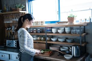 キッチンで野菜を切っている女性の素材 [FYI01078486]