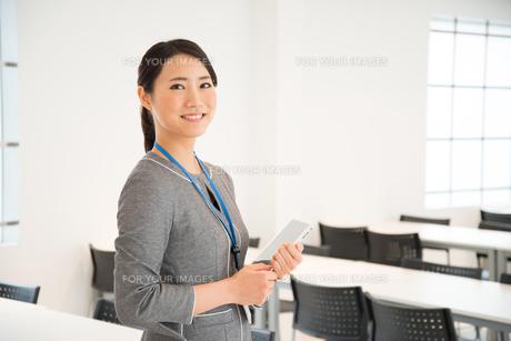 タブレットを抱えて笑っている女性の素材 [FYI01078489]