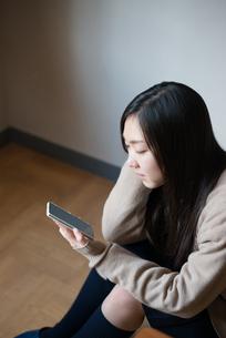 座って携帯電話を触っている女子高校生の素材 [FYI01078492]
