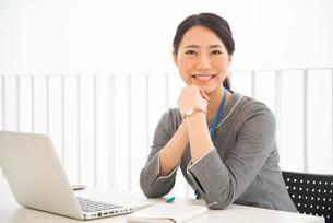 パソコンの前で笑っている女性の素材 [FYI01078493]