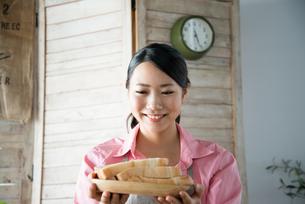 食パンを持って笑っている女性の素材 [FYI01078494]