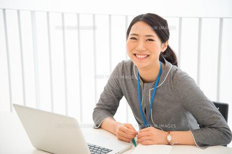 パソコンの前で笑っている女性の素材 [FYI01078497]